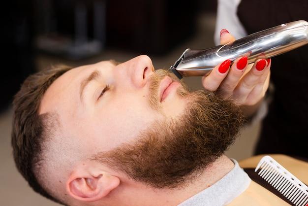 彼女のクライアントの口ひげのクローズアップを剃る女性
