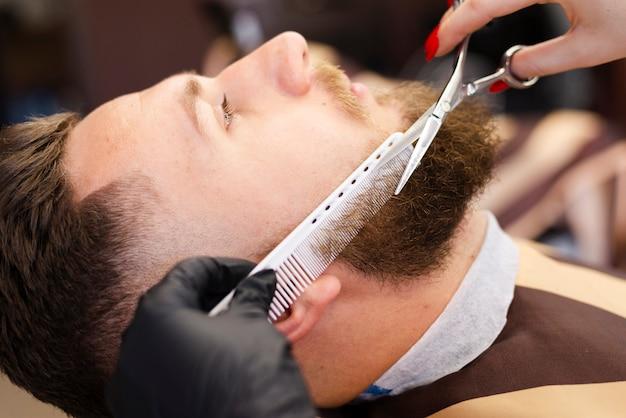 Женщина режет бороду клиента крупным планом