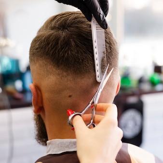 Вид сзади женщина обрезает волосы своего клиента крупным планом