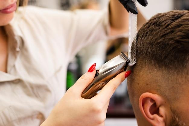 Женщина режет мужской волос крупным планом