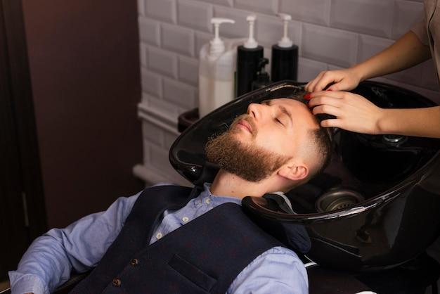 Женщина моет волосы клиента в парикмахерской