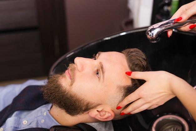 理髪店のクローズアップでクライアントの髪を洗う女