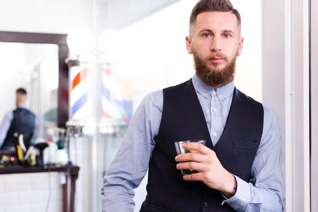 Мужчина позирует с напитком в салоне