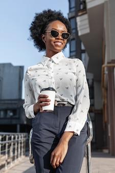 バルコニーでコーヒーを飲みながら若い女性