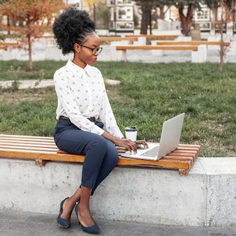 Высокий угол модер женщина, работающая на скамейке