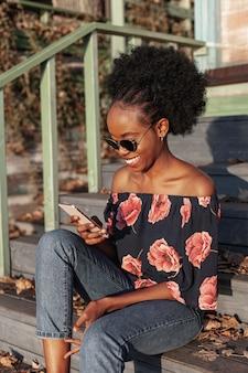 彼女の電話で見ているカジュアルなアフリカ女性