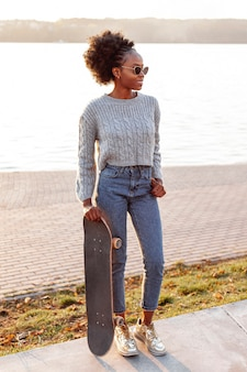 スケートボードを保持しているロングショットの若い美しい女性