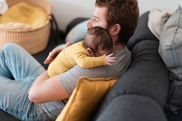 ソファの上のミディアムショットの父ハグ赤ちゃん