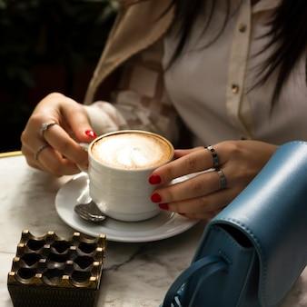 Женщина держит чашку капучино