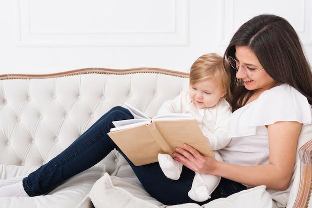 ソファで赤ちゃんと一緒に読んでいる女性