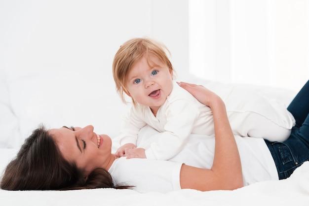 Мать держит улыбающегося ребенка