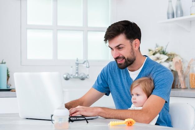 Отец работает на ноутбуке, держа ребенка