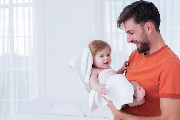 Отец держит ребенка в полотенце