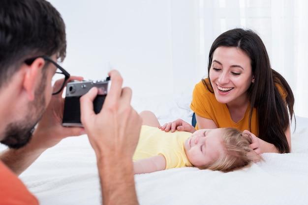 父は母親と赤ちゃんの写真を撮る