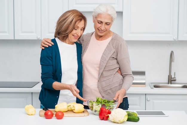 テーブルの上の野菜を持つ高齢者の女性