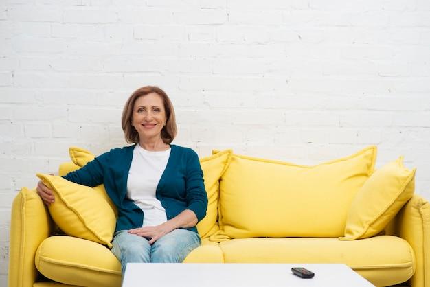 Красивая старшая женщина на диване