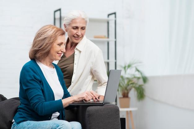 Зрелые друзья просматривают на ноутбуке