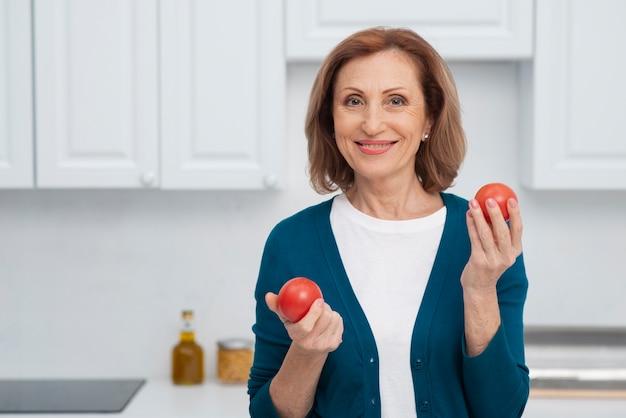 トマトを保持している幸せな女性の肖像画