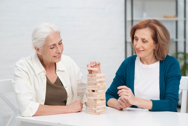 ジェンガを一緒に遊ぶ年配の女性