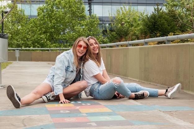 Вид спереди подруги сидят на детской площадке