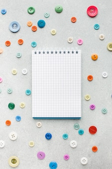 Пустой блокнот в окружении красочных кнопок