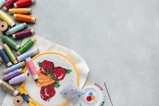 Разноцветные швейные нитки и иголки с копией пространства