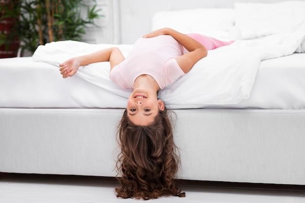 Низкий угол девушка на краю кровати с головой висит