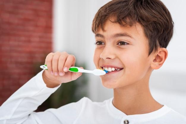 Вид спереди молодой мальчик чистит зубы