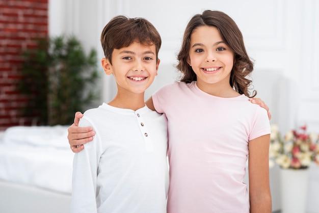 Вид спереди братьев и сестер в домашних условиях обниматься