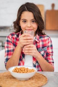 朝食で新鮮なジュースを飲む高角の女の子