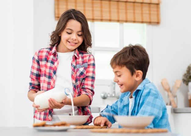 Старшая сестра наливает молоко для младшего брата