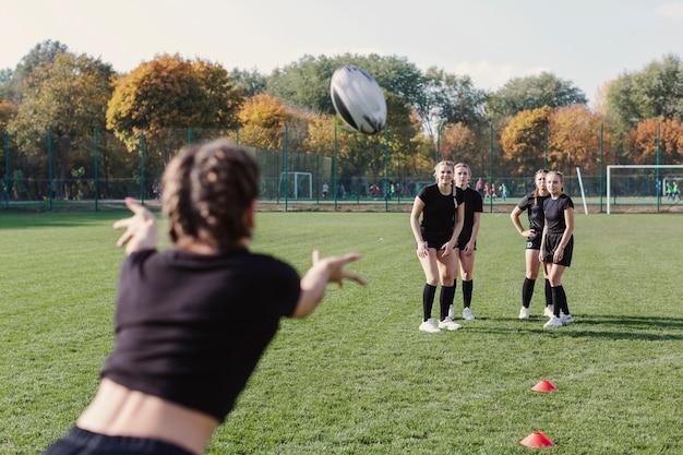 サッカーボールを渡す背面図女性
