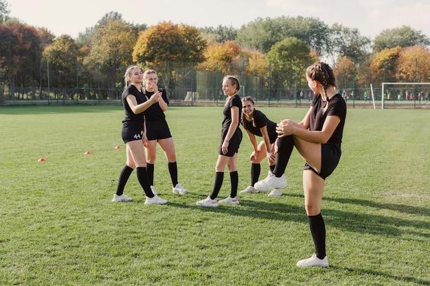 サッカーのフィールドでウォーミングアップの女性