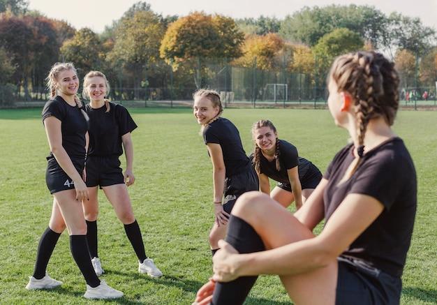 サッカーのフィールドでウォーミングアップの女の子