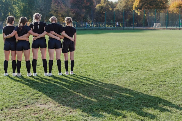 サッカーのピッチに立っている背面図の女の子