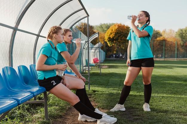若いフットボール選手は水を飲む