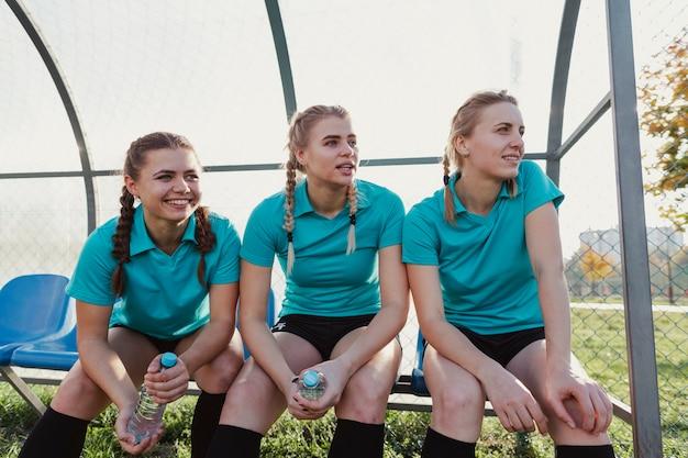ベンチに座ってサッカー用品の女性