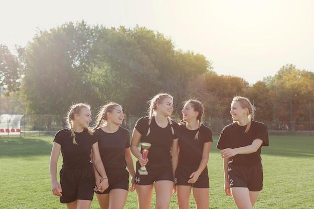 トロフィーを保持している正面の女子サッカー選手