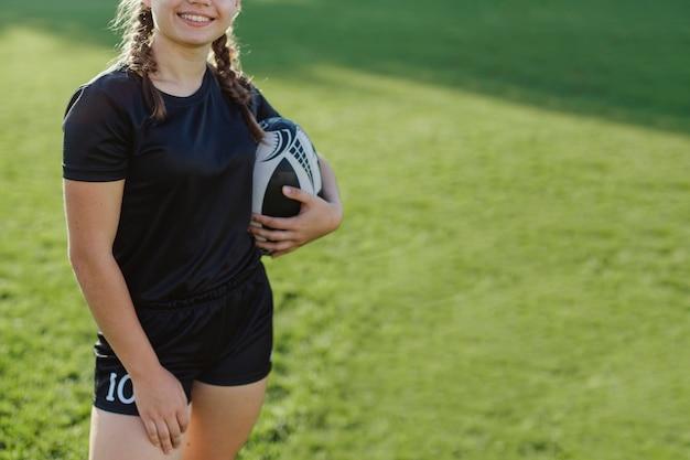 ラグビーボールを保持している女性の笑みを浮かべてください。
