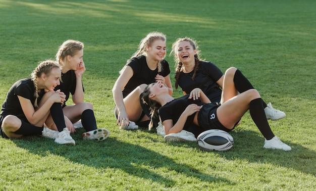 草の上に座っている女性のラグビーチーム