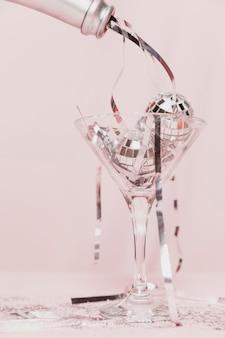 ガラスに見掛け倒しを注ぐシャンパンボトルのクローズアップ
