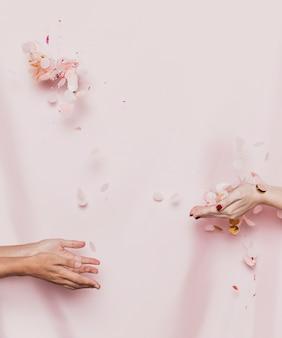 繊維の背景を持つ花びらを投げている手