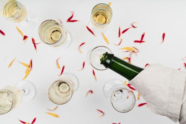 Вид сверху шампанское, льющееся в бокал