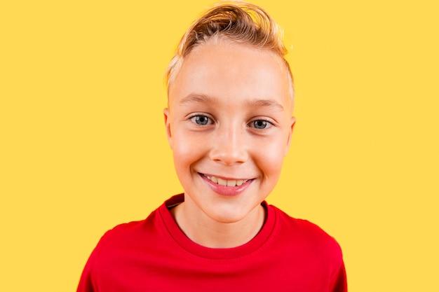 黄色の背景に笑みを浮かべて肖像若い男の子