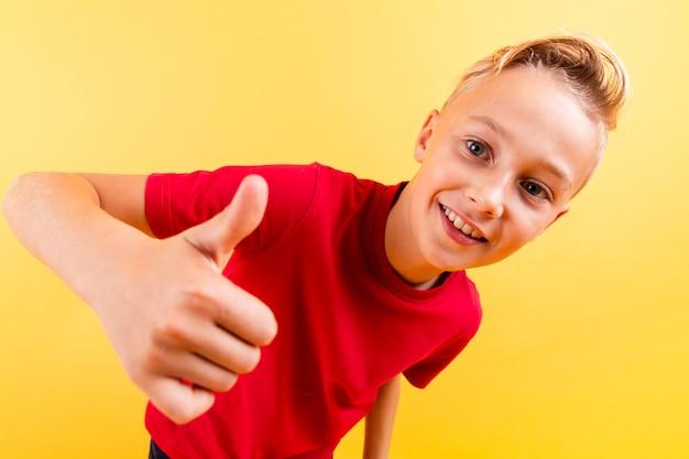 Высокий угол молодой мальчик показывает знак ок