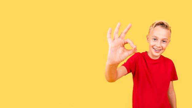 Вид спереди смайлик молодой мальчик показывает знак ок
