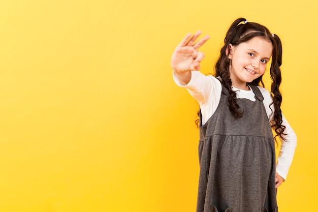 Копия пространство маленькая девочка показывает знак ок