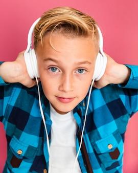 上のヘッドフォンで高角度の小さな男の子