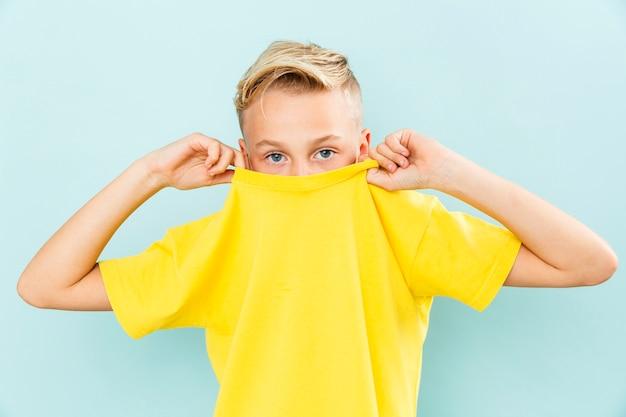 Мальчик вид спереди стягивая свою футболку