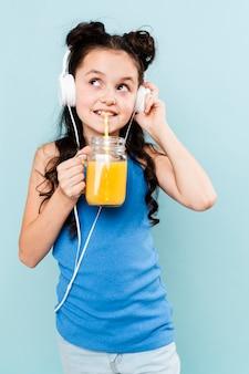 フロントビューの女の子がジュースを飲むと音楽を聴く
